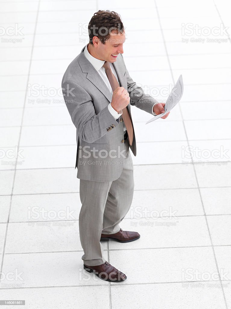 Young successful happy business man standing and  reading royalty-free stock photo