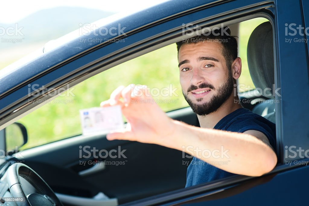 young successful man in car showing new european driving license stock photo