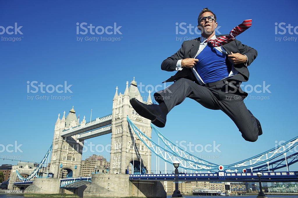 Young Superhero Businessman Jumping Over Tower Bridge London stock photo