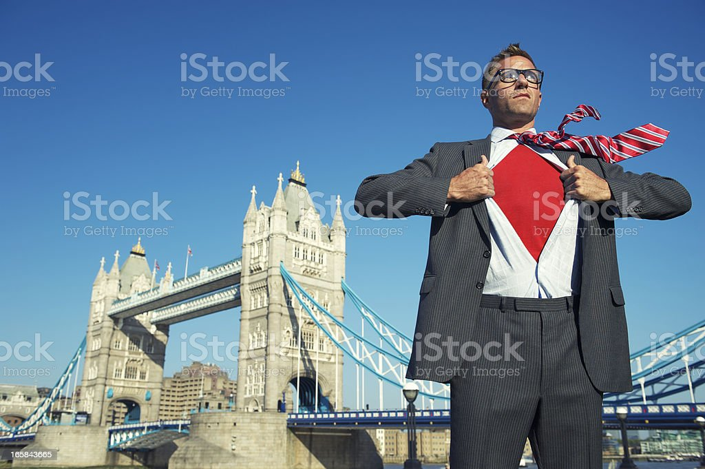 Young Superhero Businessman Reveals Red Chest at London Skyline royalty-free stock photo