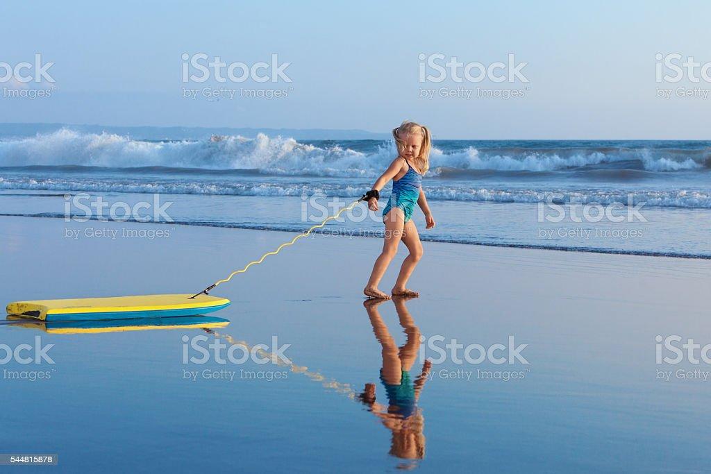 Young surfer girl with bodyboard walks along beach sea surf stock photo