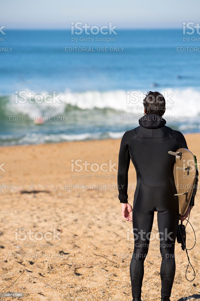 Young surfer man standing on the beach stock photo