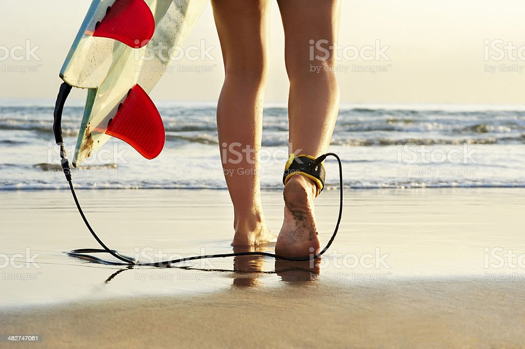 young surfer walking towards the surf with ankle leash stock photo
