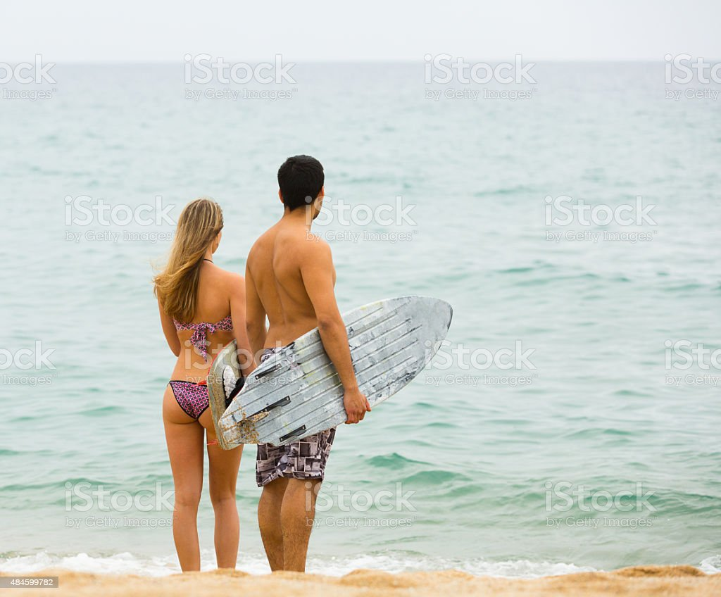 Young surfers couple on the beach stock photo
