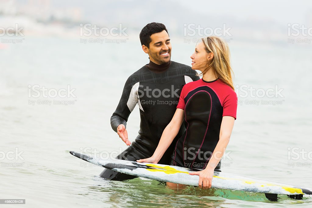 Young surfers family waist deep in water stock photo