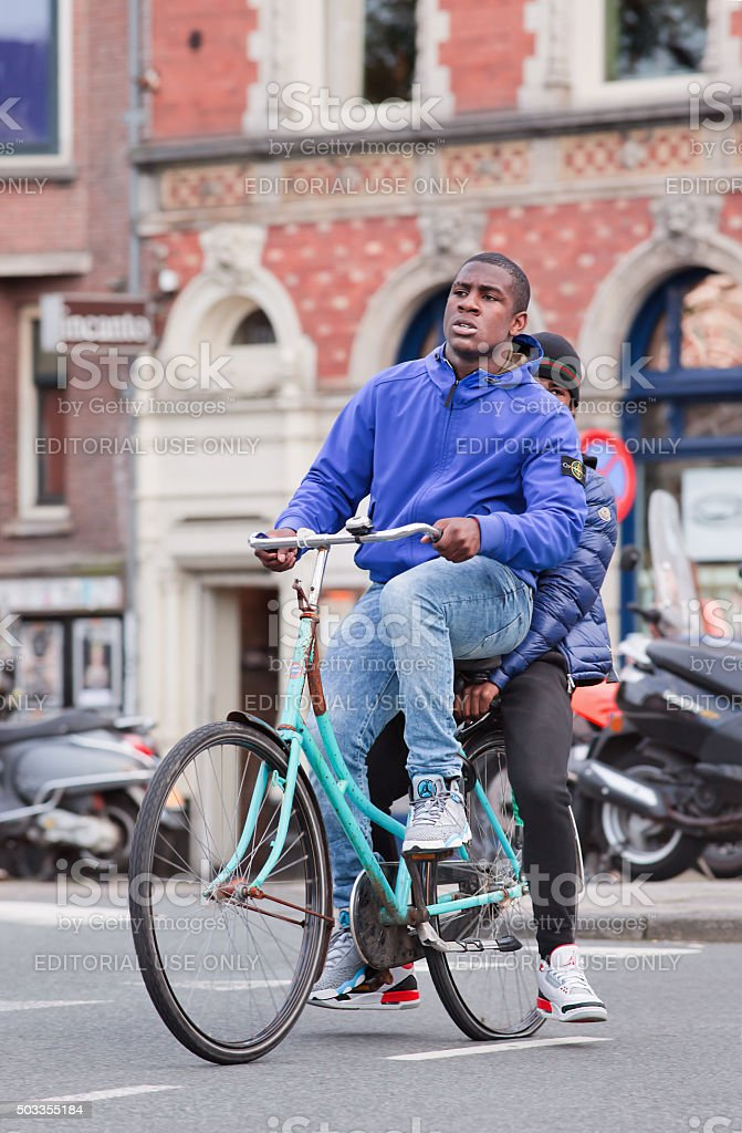 Young Surinam guy on a blue bicycle with classic building stock photo