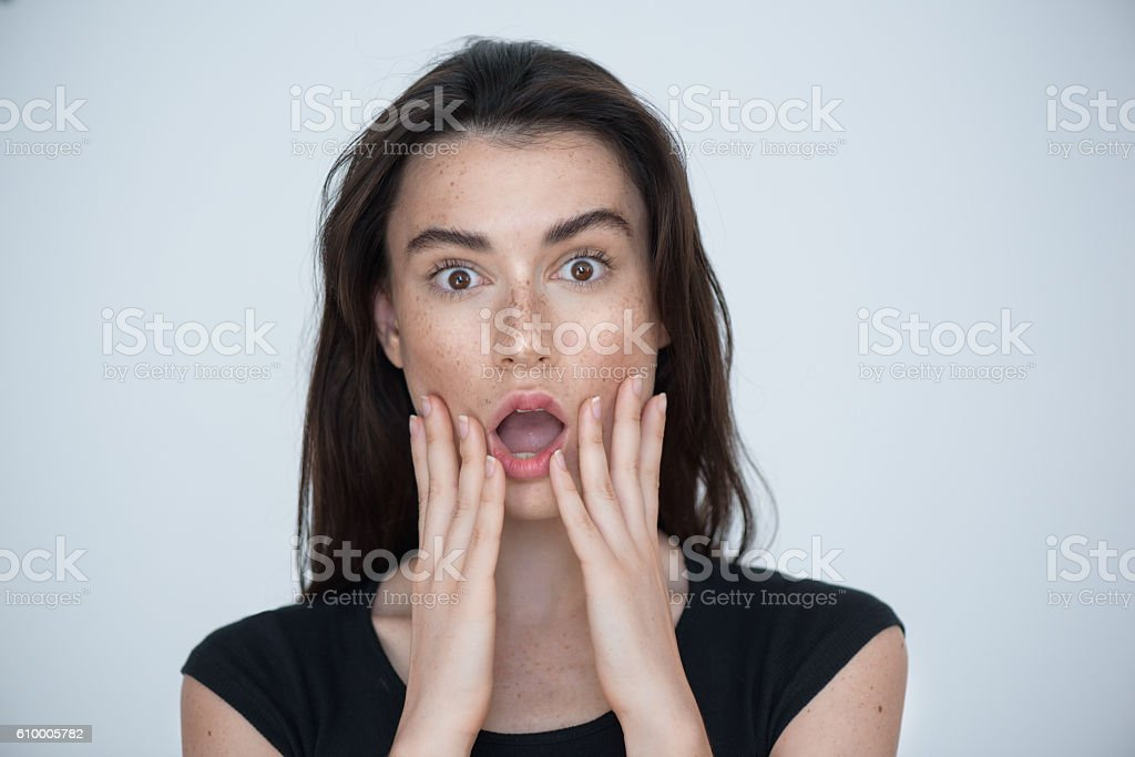 young surprised brunette posing in the studio stock photo