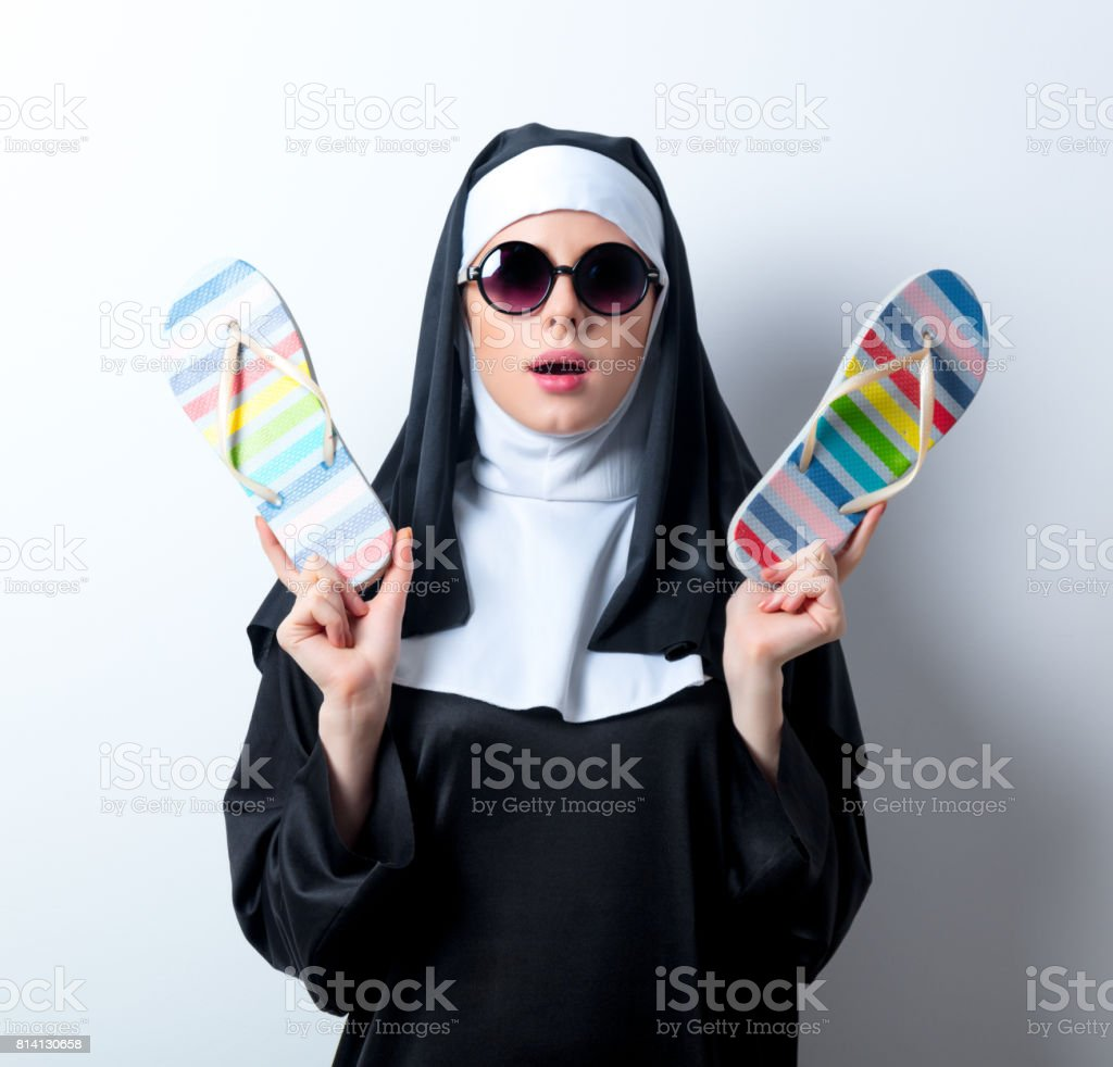 Young surprised nun in sunglasses with flip flops stock photo