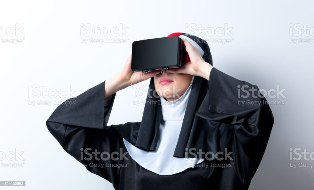 Young surprised nun with virtual reality glasses stock photo