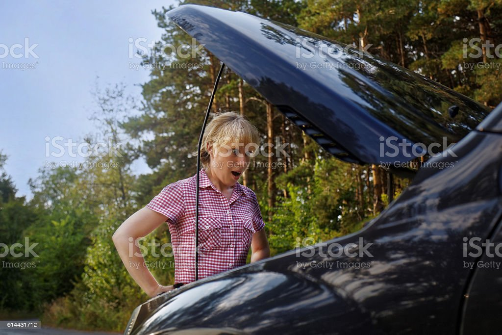 Young surprised woman looking at the car engine stock photo