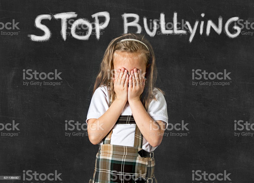 young sweet junior schoolgirl victim of bully crying sad standing in...