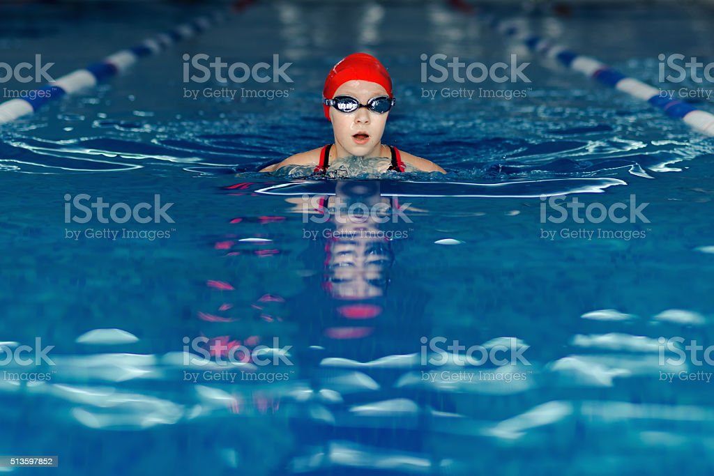 young swimmer girl in swimming pool stock photo