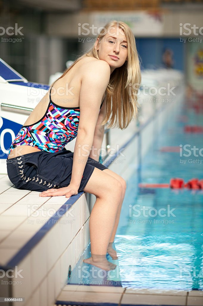 Young Swimmer Resting At Starting Block stock photo