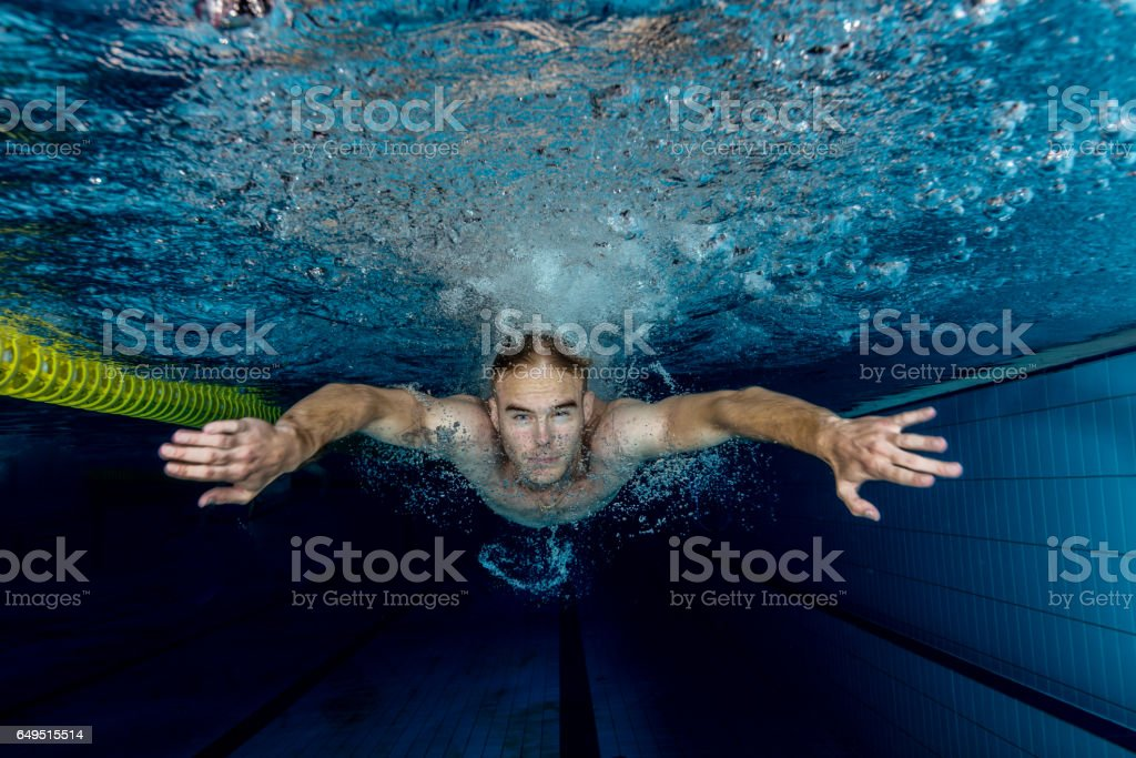 Young swimmer swimming in a pool underwater stock photo