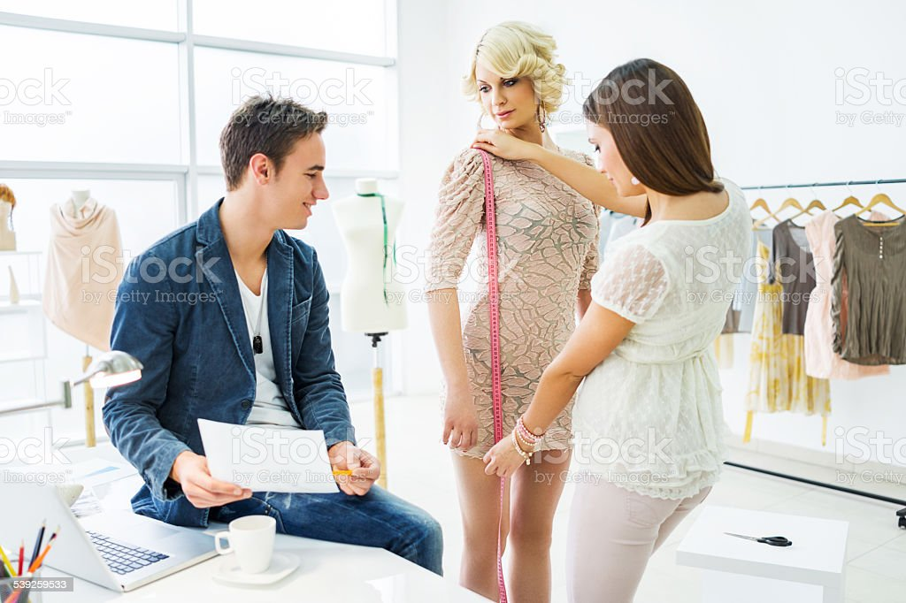 Young tailors with their client. stock photo