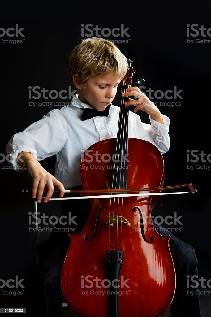 Young talented boy playing cello stock photo