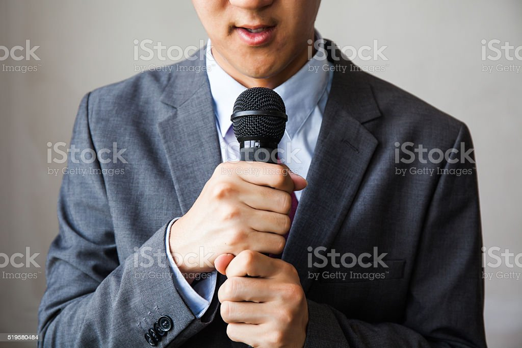 Young talking man holding microphone without confidence stock photo