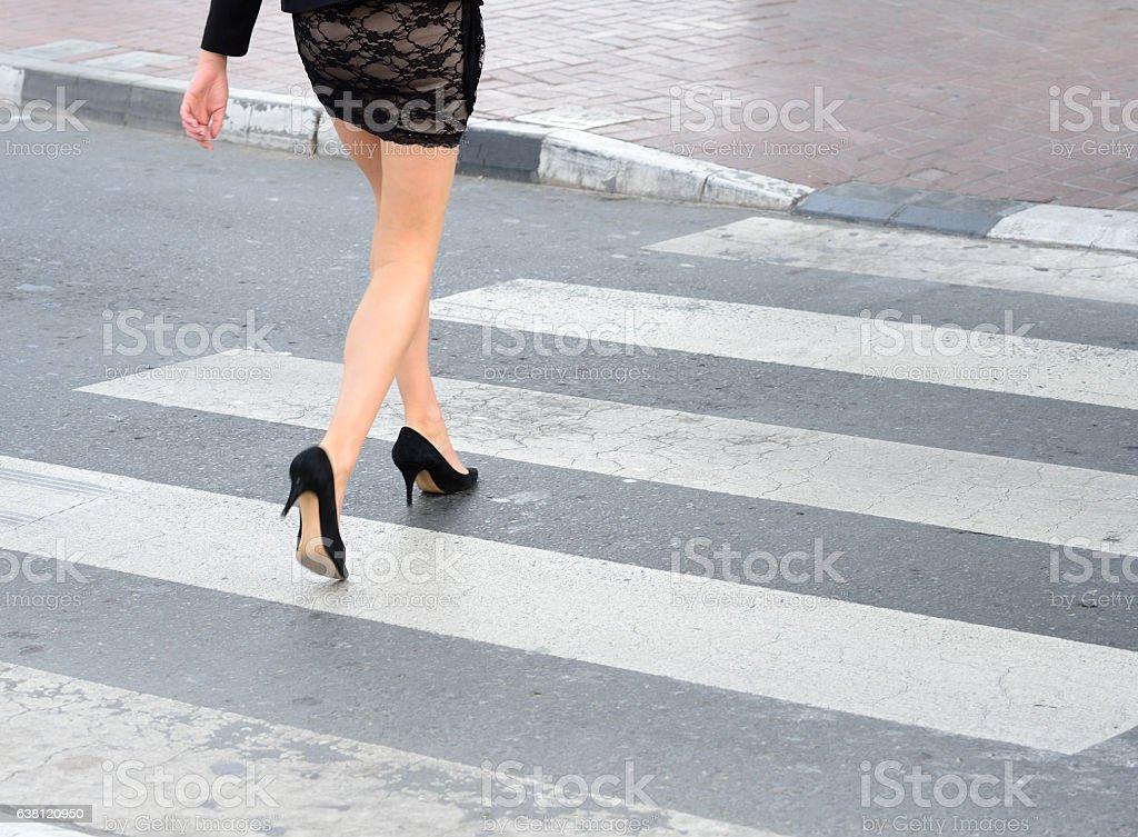 Young tall woman crossing Dubai street on zebra crossing stock photo