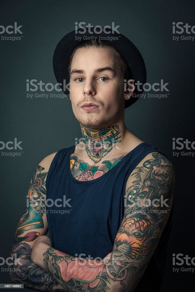Young tattooed man standing arms crossed stock photo