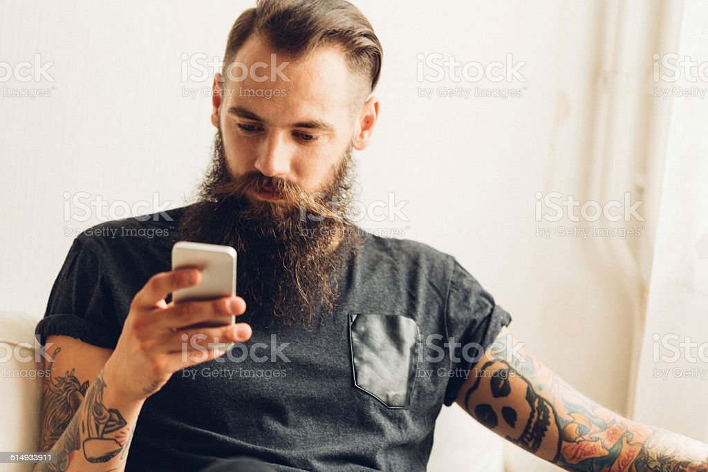 young tattooed man using mobile phone stock photo