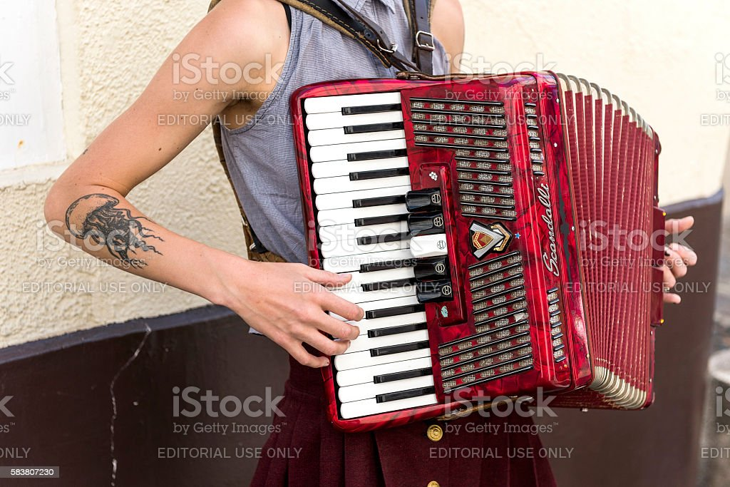 Young tattooed woman musician plays accordion in Montmartre, Paris stock photo