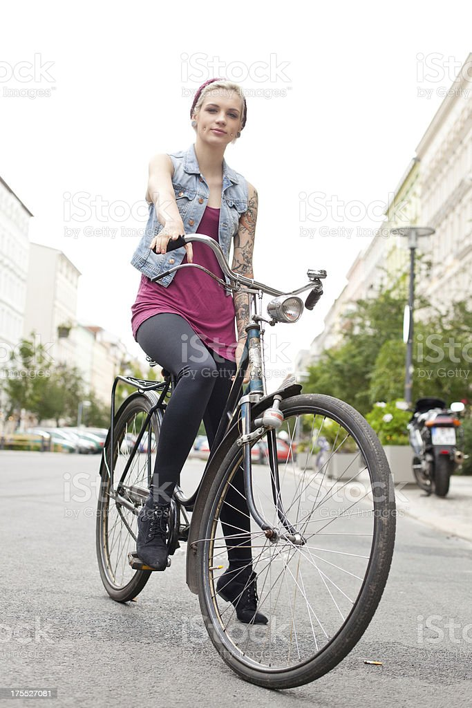 Young tattooed woman on her bicycle stock photo