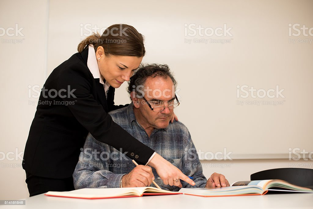 Young teacher explaining somethng to eldery man.  Intergenerational transfer knowledge. stock photo