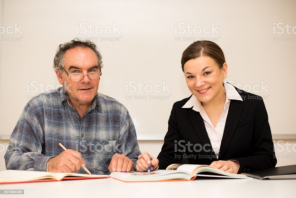 Young teacher explaining somethng to eldery man. stock photo