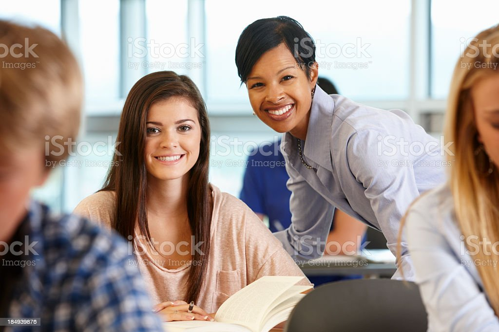 A young teacher helping a student while both smile in class stock photo