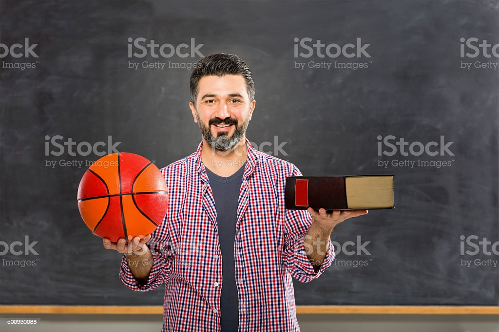 Young teacher holding ball and encyclopedia. stock photo