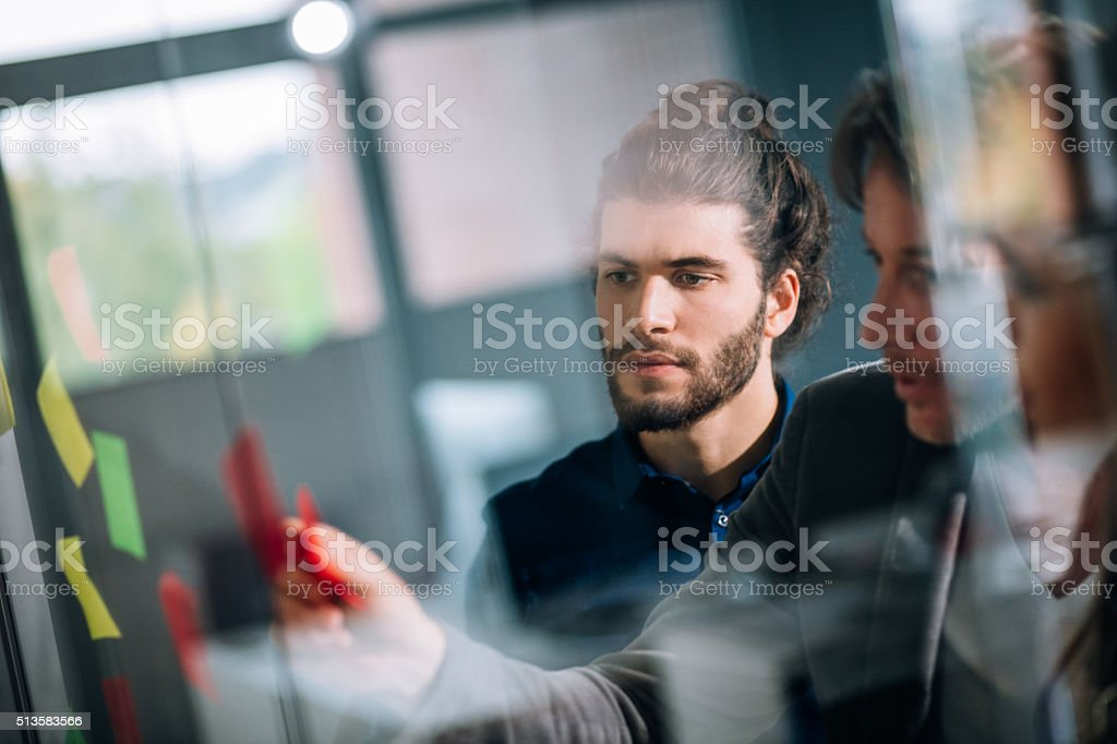 Young team listening attentively to team leaders brainstorm concept stock photo