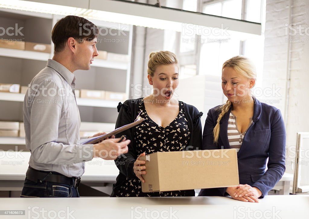 young team looking at surprise parcel royalty-free stock photo
