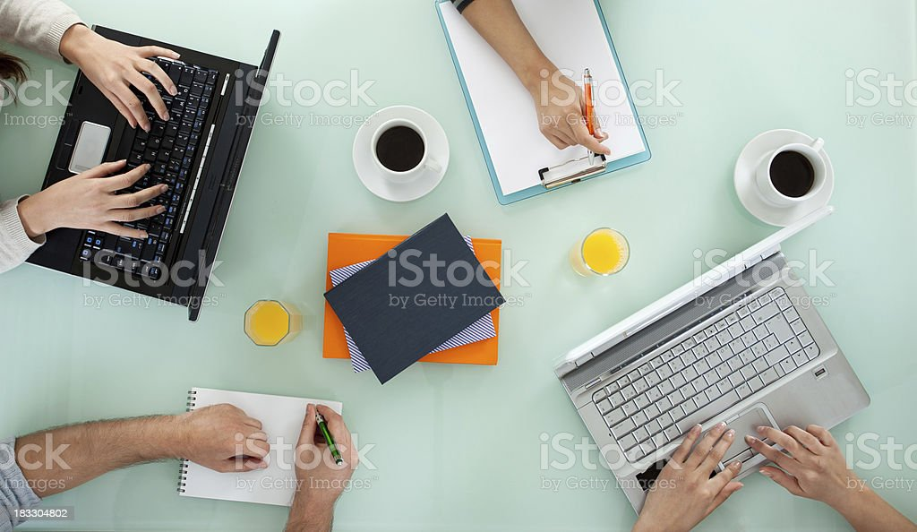 Young team working on laptop computers and writing stock photo