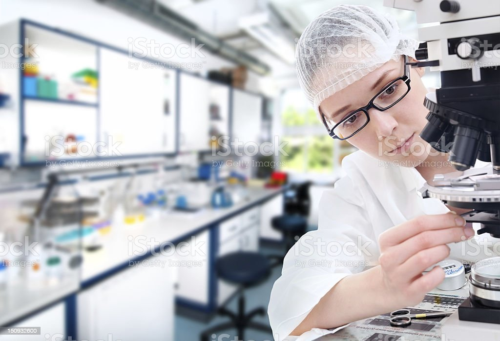 Young tech tunes her microscope stock photo