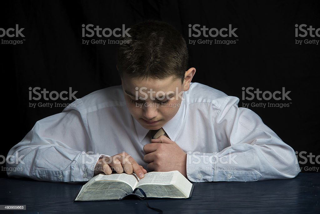 young teen boy studying the scriptures stock photo