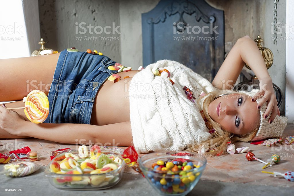 Young teen eats candies in a living room royalty-free stock photo