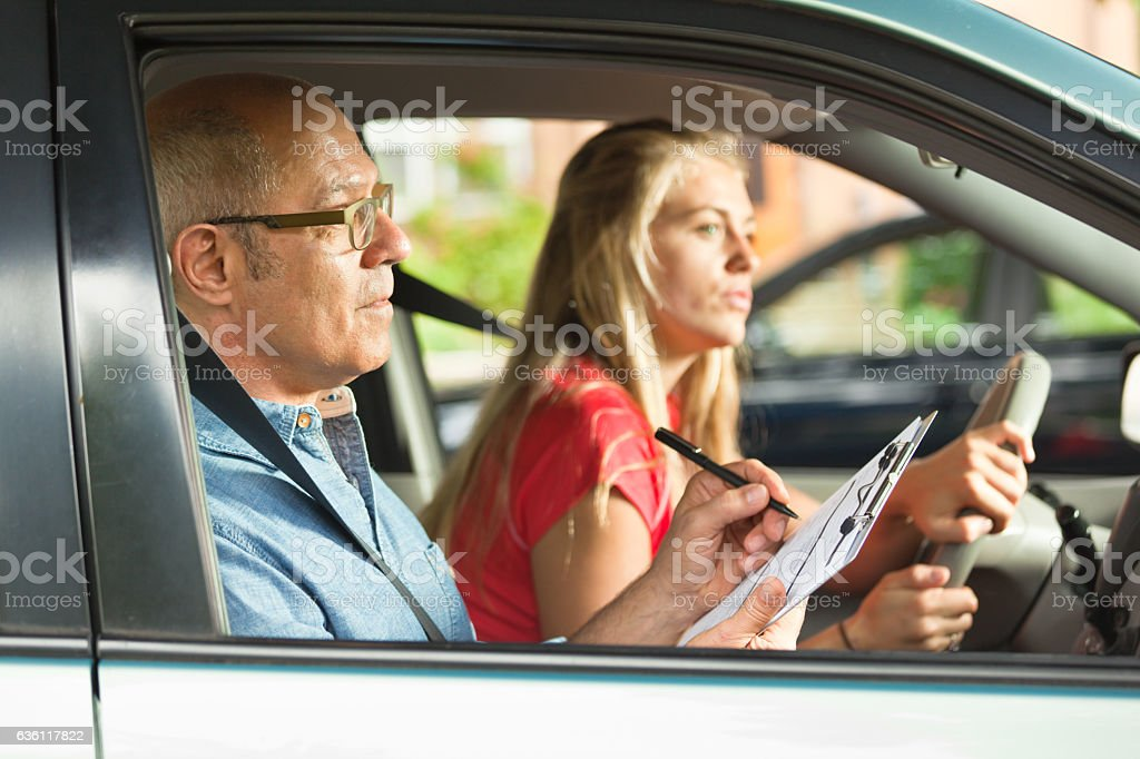 Young Teen Girl Doing Driving Exam with Examiner stock photo