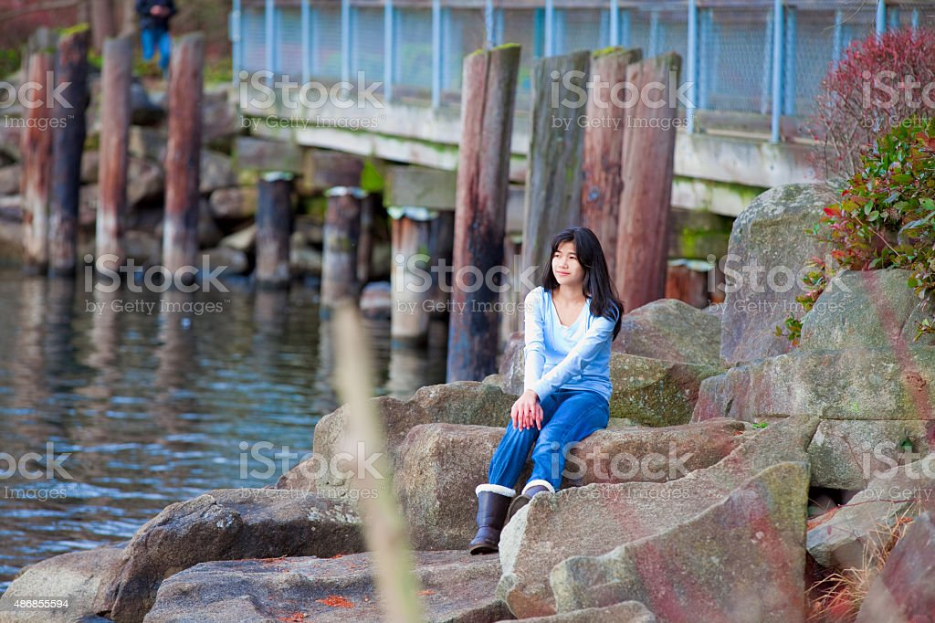 Young teen girl sitting on large boulders along lake shore stock photo