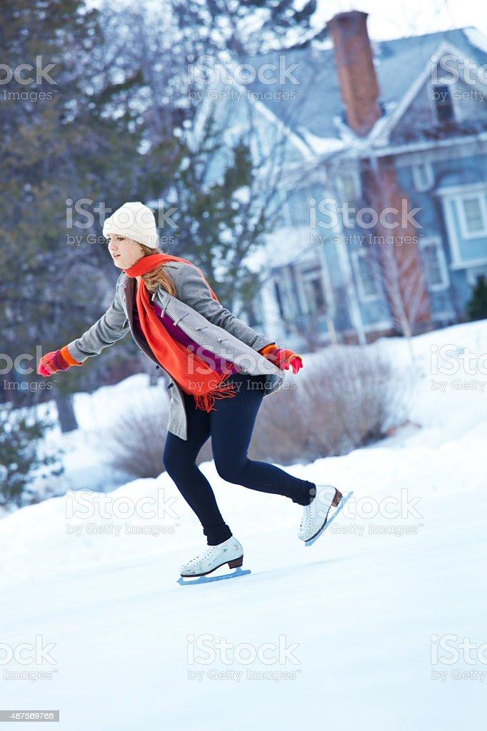 Young Teen Girl Skater Enjoying Winter Outdoor Skating Rink stock photo
