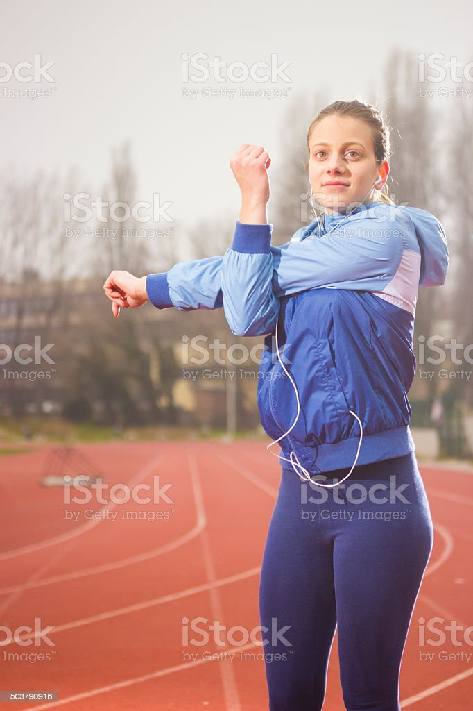 Young teen girl, stretching on sports field, preparing stock photo