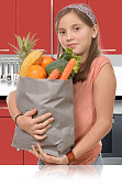 Young teen, holding grocery shopping bag with vegetables Standin