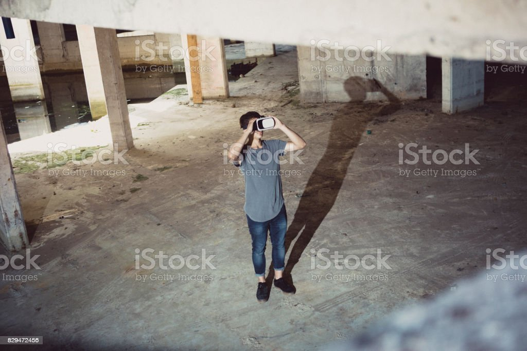 Young teenage boy using virtual reality in the basement stock photo