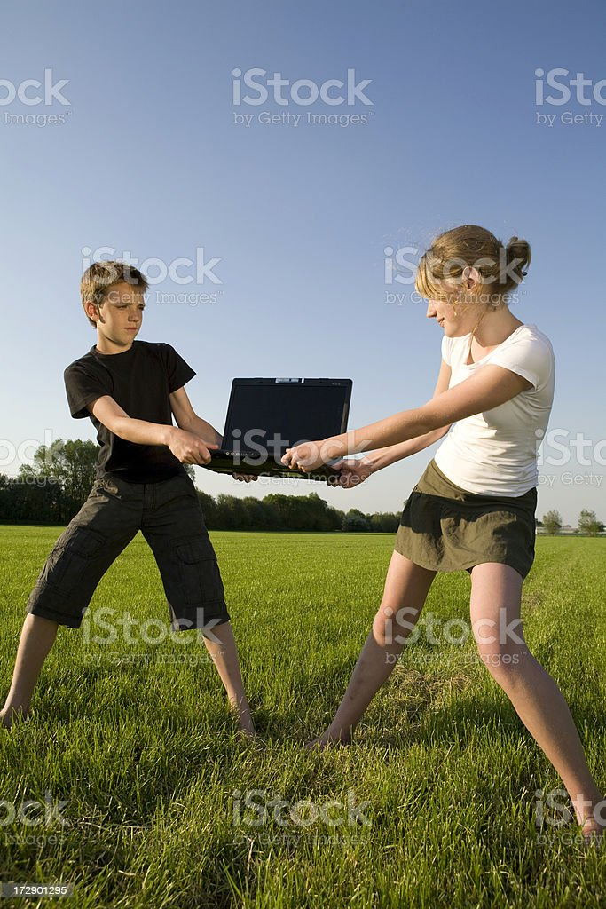 Young teenage girl and boy are arguing for a labtop. royalty-free stock photo