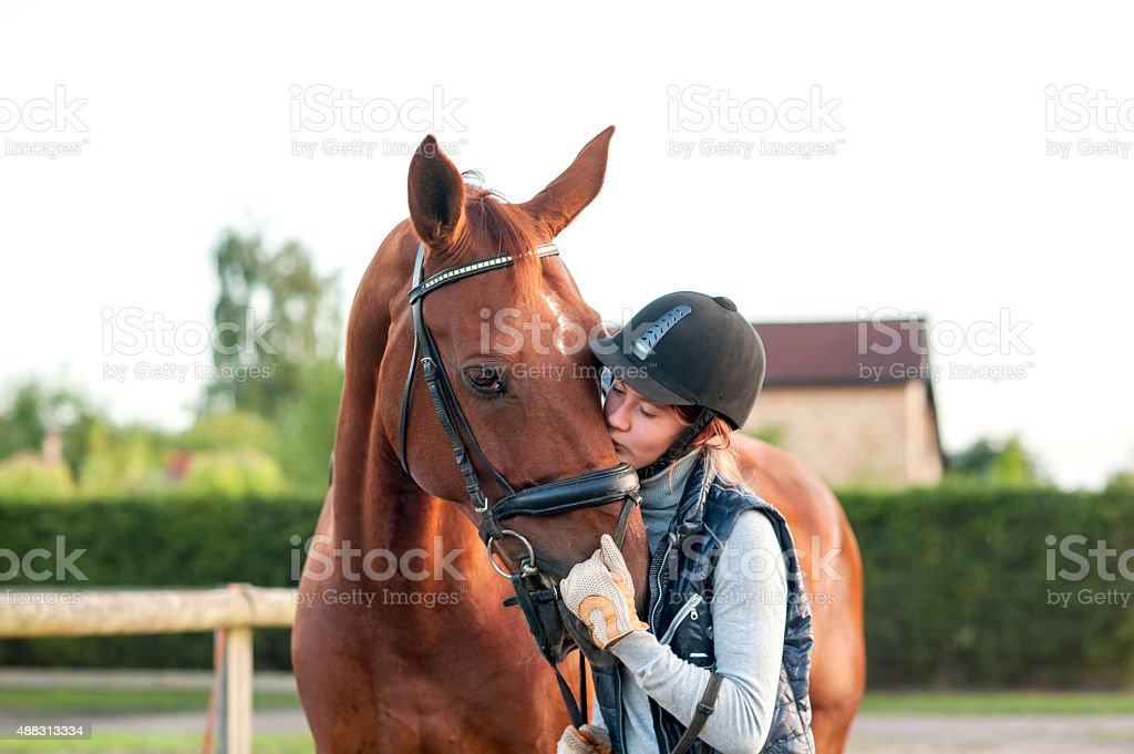 Young teenage girl equestrian kissing her chestnut horse. stock photo