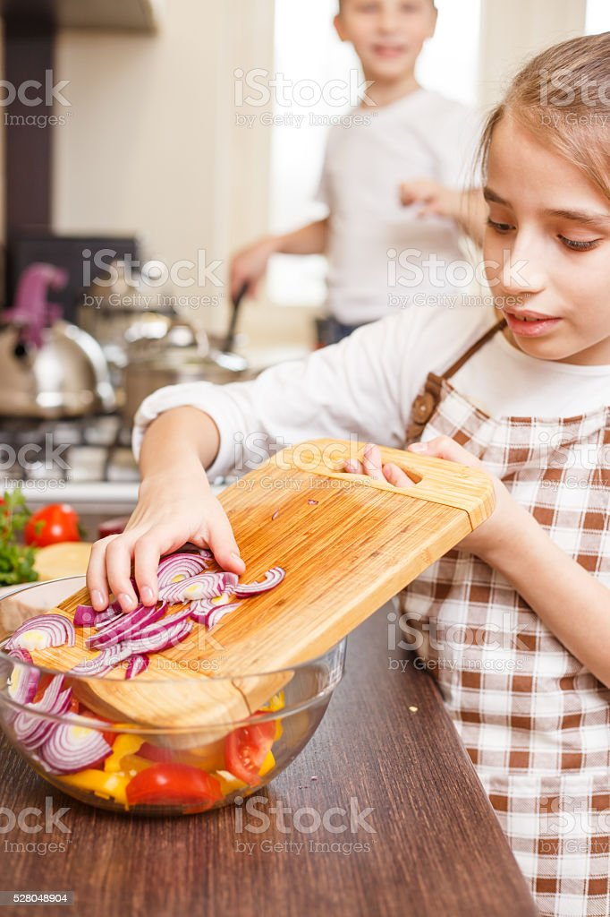 Young teenage girl in apron mixing salad vegetables stock photo