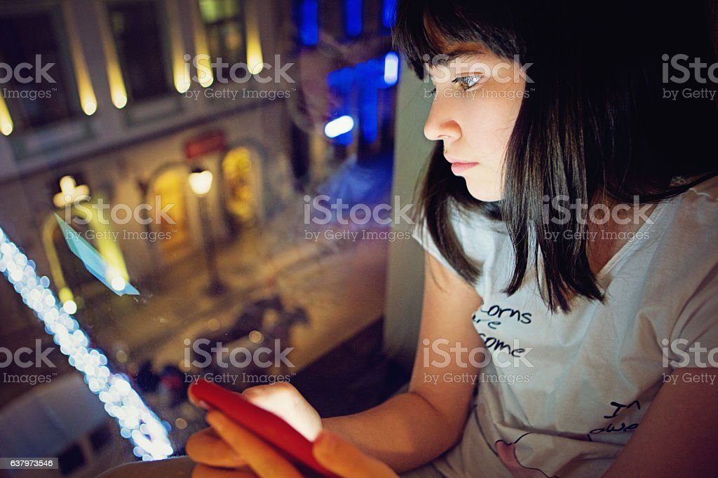 Young teenage girl is texting on the window stock photo