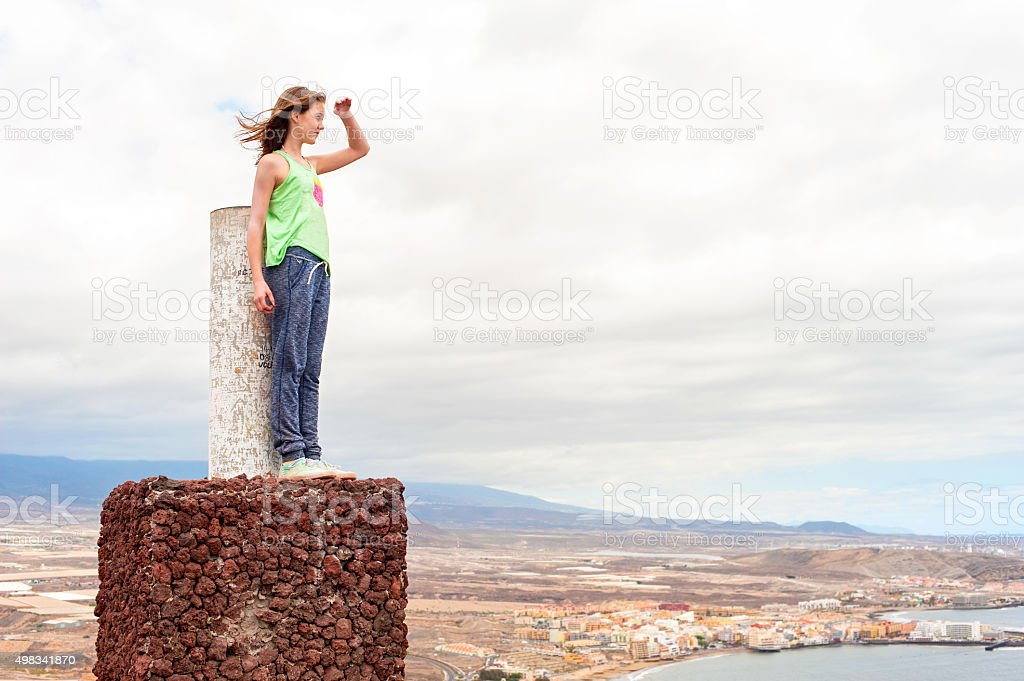 Young teenage girl on mountain peak looking over panoramic view stock photo