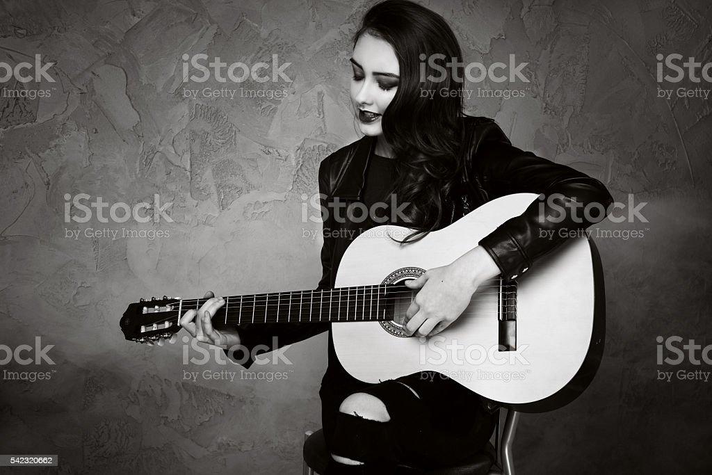 Young teenage girl playing on guitar. stock photo