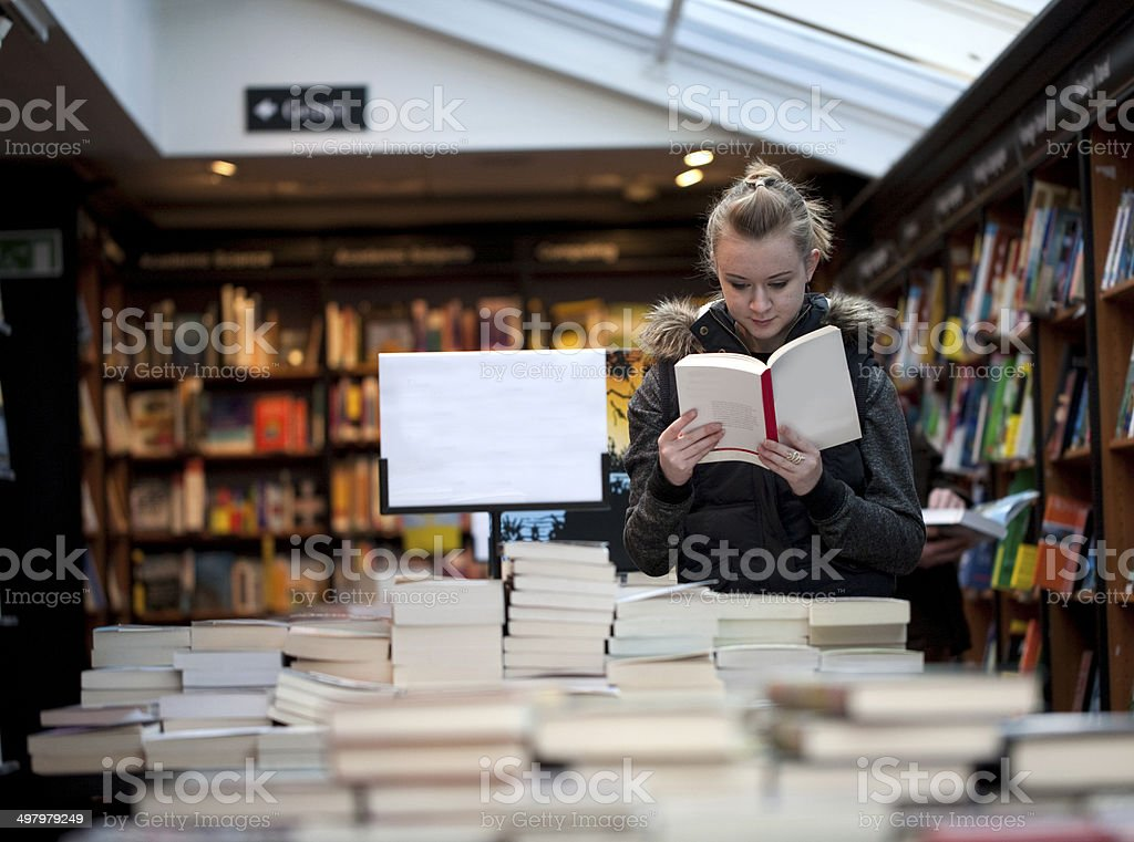Young teenage girl reading in bookstore stock photo