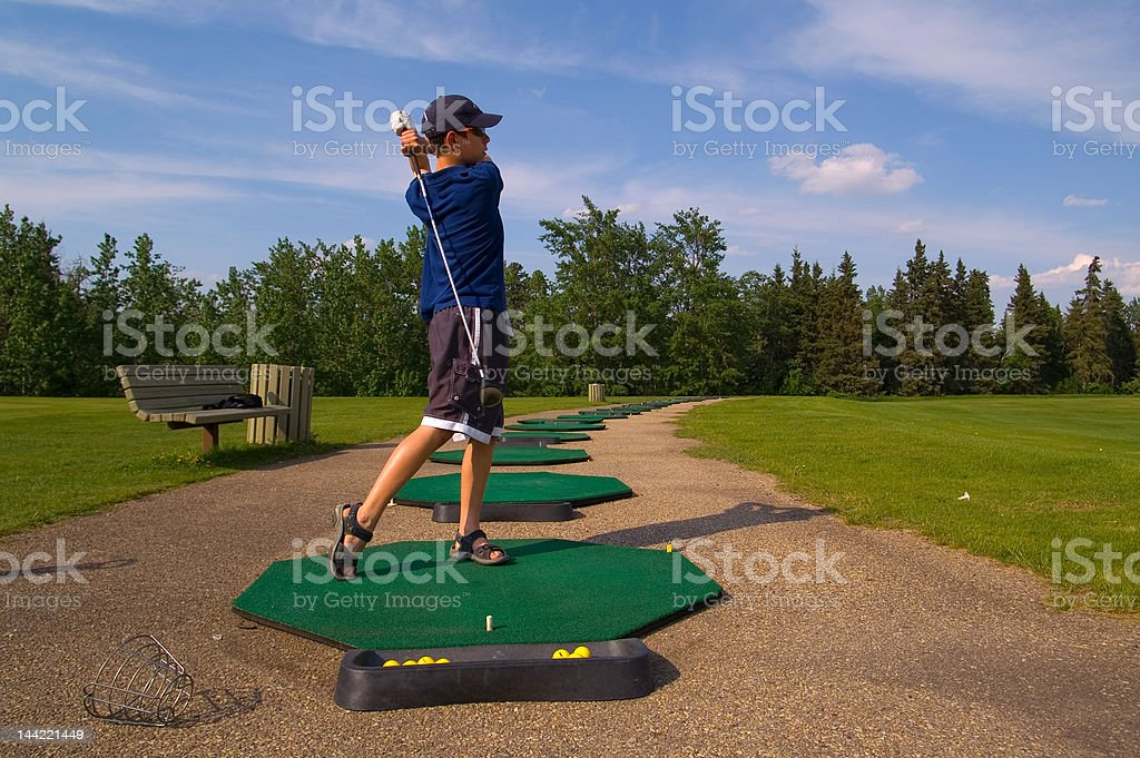 Young Teenage Golfer at Driving Range stock photo